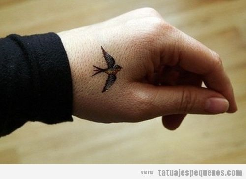 Tatuaje de un pájaro pequeño en la mano de un chico