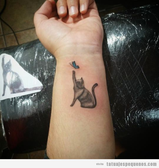 Tatuaje pequeño gato y mariposa en la muñeca