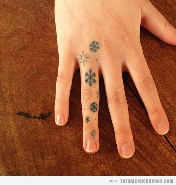Tatuajes pequeños copos de nieve en los dedos mano