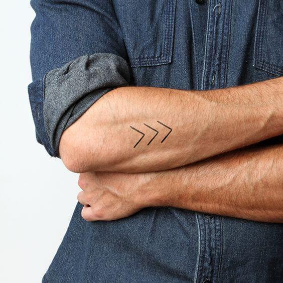 Tatuaje pequeño hombre brazo flechas minimalistas